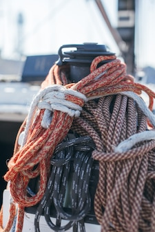 Nautical ropes, buntine, capstan and cablet piled up on deck of professional racing yacht or sailboat, attached to mast or forestay, different colors