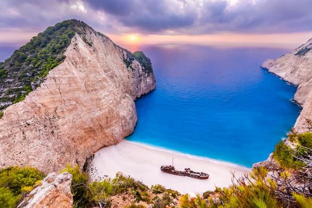 Пляж навагио с кораблекрушением на закате острова закинф, греция