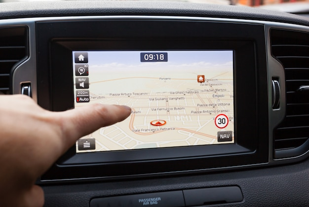 Navigation panel inside a car. finger pointing on destination point.