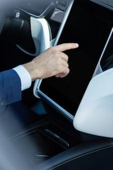 Навигатор в машине. крупным планом бизнесмена в костюме с помощью навигатора в машине, направляясь по неизвестному адресу