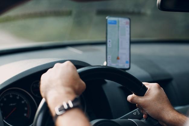 자동차 차량 운송 통근의 내비게이터. 차를 운전하는 동안 휴대 전화 내비게이터 앱을 사용하는 운전자 남자