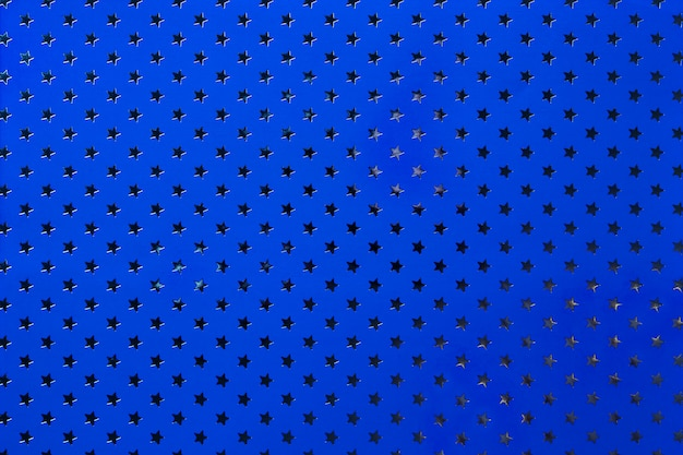 Navy blue background from metal foil paper with a silver stars pattern.
