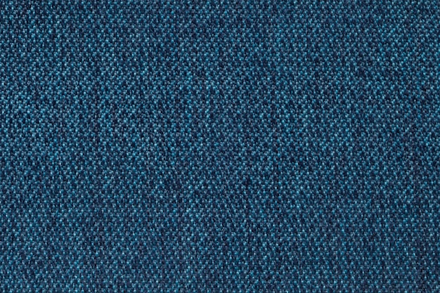 Navy blue background from woolen texture textile, closeup. structure of the wicker fabric macro.