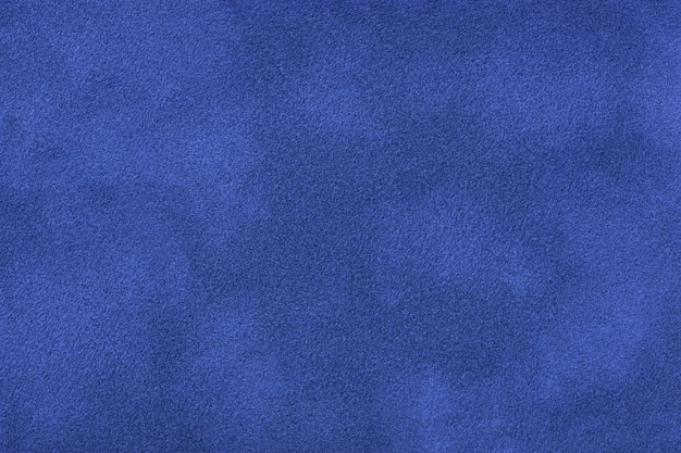 Navy blue matte background of suede fabric, closeup. velvet texture of seamless sapphire textile, macro. structure of indigo felt canvas backdrop.