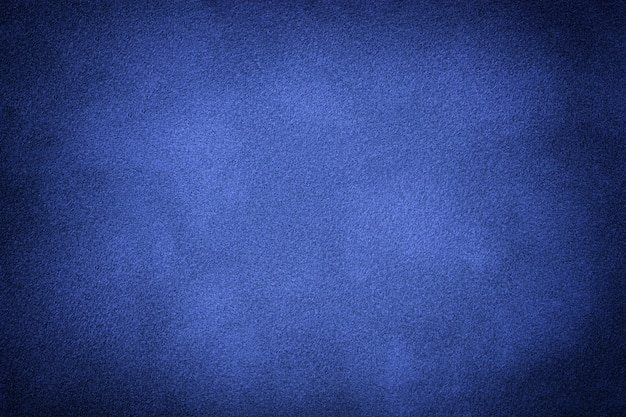 Navy blue matte background of suede fabric with vignette, closeup. velvet texture of seamless indigo textile with gradient, macro.