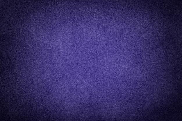 Navy blue matte felt background of suede fabric with vignette. velvet texture of indigo textile with gradient.