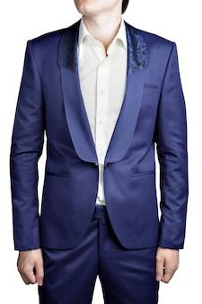 ネイビーブルーのメンズスーツジャケット、ボタンホールなし、ボタンなし、ボタンなし、クラスプチェーンクロージャー、幅広の襟付きショールカラー、上部に黒の装飾パターン、白で隔離。