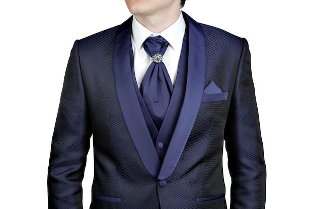 男性用のネイビーブルーのスーツ、結婚式やウエディング、ベスト、シャツ、ブローチ付きネクタイプラストロン、クローズアップ、白い背景で隔離。