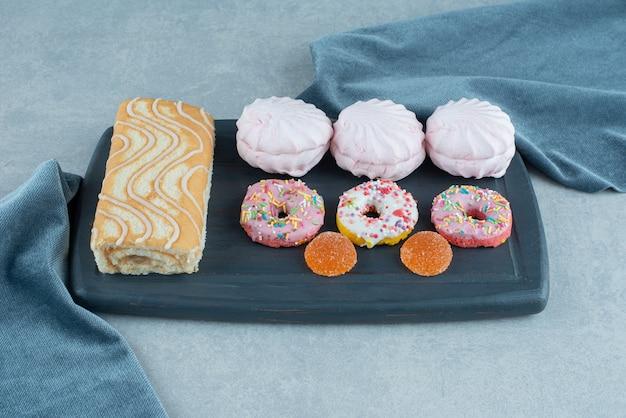 Bordo della marina con un rotolo di torta, biscotti, ciambelle e marmellate su marmo.