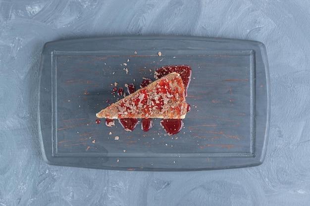 대리석 표면에 딸기 시럽으로 맛을 낸 케이크 조각이있는 네이비 플래터.