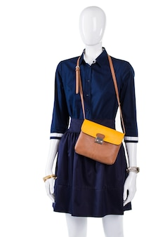 Navy shirt with bicolor purse. mannequin wearing thin bicolor bag. woman's new leather handbag. dark outfit with light purse.