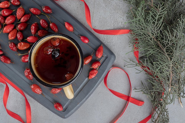Темно-синий поднос из плодов шиповника и кружка чая из шиповника в окружении лент на мраморном столе.