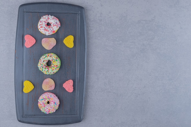 대리석 표면에 marmelades와 도넛이있는 해군 나무 보드