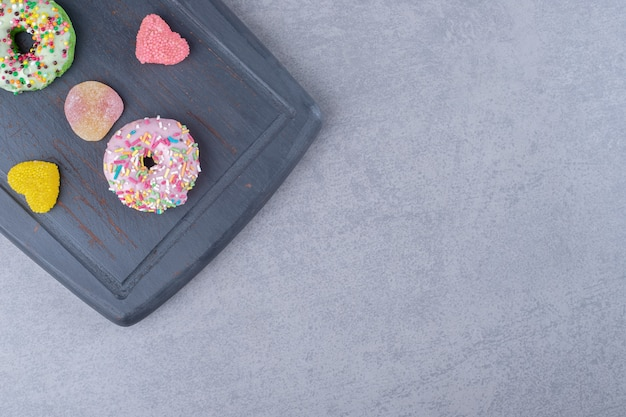 Navy wooden board with marmelades and donuts on marble surface