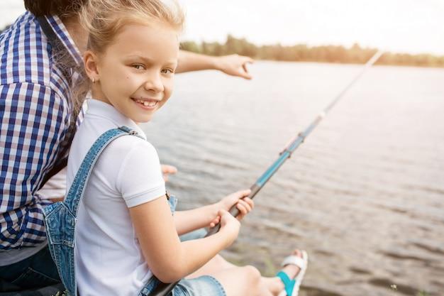 男は娘ndが前方を向いて川岸に座っています。女の子は魚棒を保持しているとカメラ目線です。彼女は微笑んでいる。女の子は幸せそうです。
