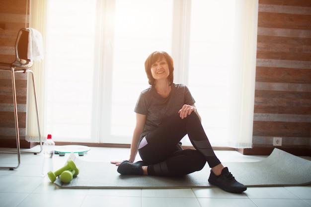 大人のフィットスリムな女性は自宅でトレーニングをしています。肯定的な陽気な年配の女性は、休憩を行使中にヨガマットndポーズに座る。高齢者の身体にフィットする美しい女性。