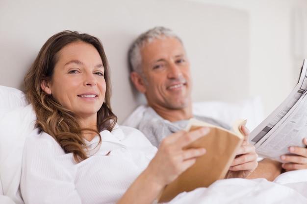 Улыбка женщины, читающей книгу, пока ее муж читает ne