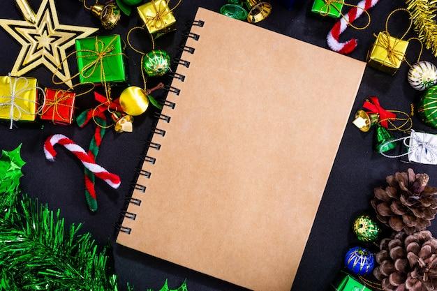 空のノートブックと黒い紙の背景、neに鉛筆でクリスマスのお祝いデコレーション