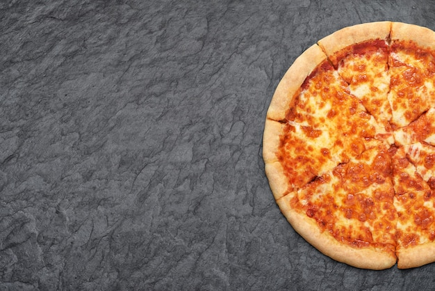 Neapolitan pizza margherita with with tomatoes and mozzarella cheese on black slate background.