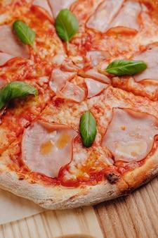 ナポリのピザ、ハム、チーズ、ルッコラ、バジル、トマトをテキスト用のセル内のテーブルクロスのテーブルクロスに木の板にチーズを振りかけた