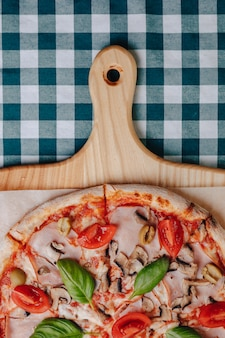 Neapolitan pizza with mushrooms, cheese, arugula, basil, tomatoes sprinkled with cheese on a wooden board on a tablecloth in a cell with a place for the text