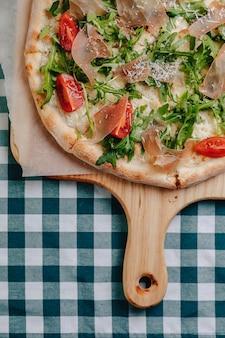 ナポリのピザ、サラミ、ルッコラ、トマト、テキストのための場所でセルのテーブルクロスの上の木の板にチーズを振りかけた