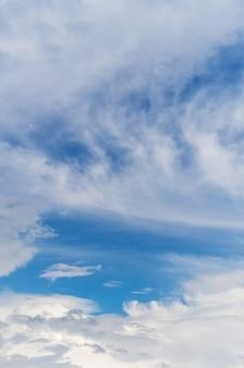 晴天の青空に浮かぶさまざまな形の雲の近く