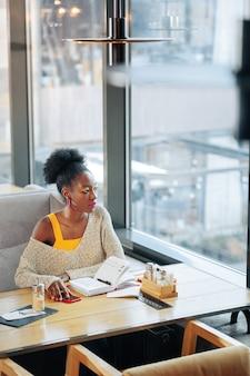 Рядом большое окно. кудрявая женщина, сидящая возле большого окна в современном ресторане