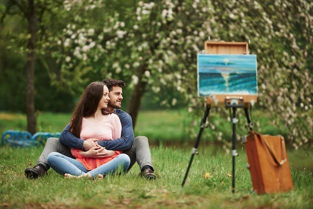 Возле мольберта. весной вместе сидеть на свежем воздухе. молодая пара обнимая