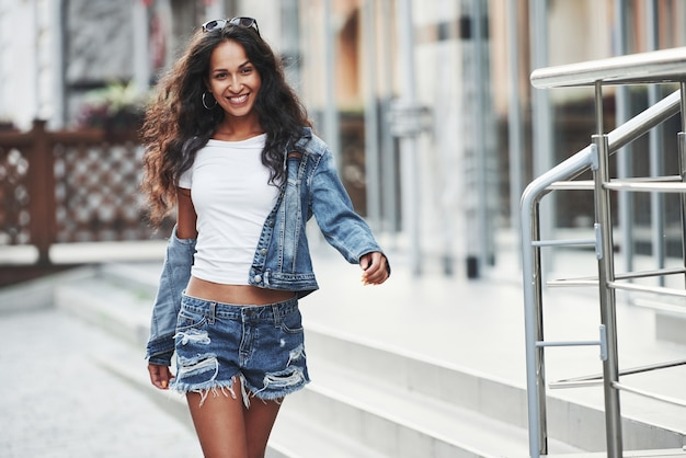 Near modern building. beautiful woman with curly black hair have good time in the city at daytime.
