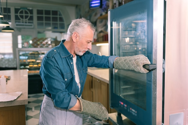Near oven. grey-haired owner of bakery wearing denim shirt standing near oven looking at baguettes