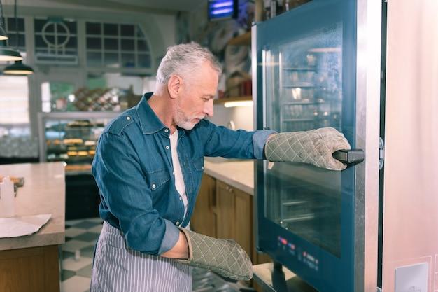 オーブンの近く。バゲットを見てオーブンの近くに立っているデニムシャツを着ているパン屋の白髪の所有者