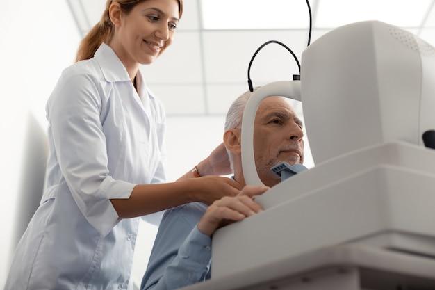 快適なクライアントに近い。心地よいクライアントの近くに立って笑っている赤毛のプロの目の専門家
