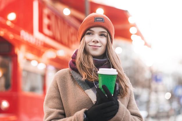 暖かい春の日に外に立って暖かい服を着て肖像画の十代の少女の近くに彼の手でコーヒーカップを持つ春の日に、素晴らしい街のボケ味を脇に