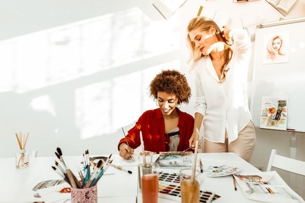 Рядом студент. стильный учитель рисования в бежевых брюках и белой блузке стоит рядом со студентом
