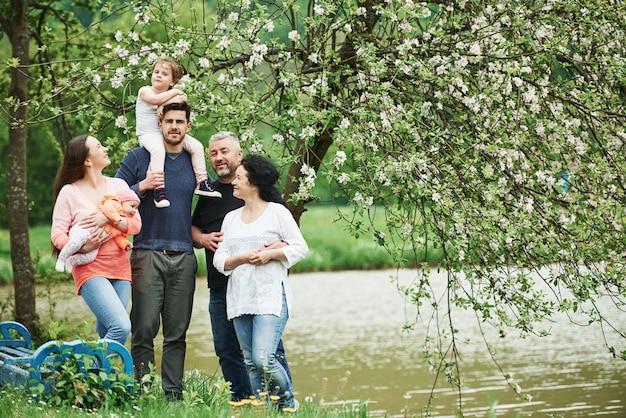ベンチと湖の近く。家族の写真。屋外で一緒に立っている陽気な人々の完全な長さの肖像画