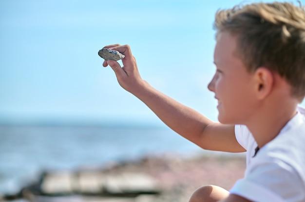 Около реки. мальчик в белой футболке бросает камни в реку