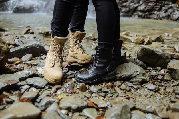 물 근처. 편안한 신발을 신고 여행하는 동안 산 강 근처의 돌에서 휴식을 취하는 활동적인 사람들