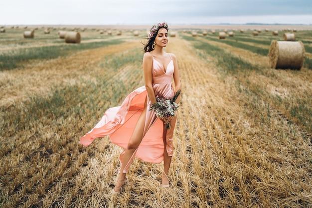 干し草のnearの近くの麦畑でピンクのサテンのドレスの若いブルネット。女性は頭に花輪を持ち、野生の花の花束を手に持っています
