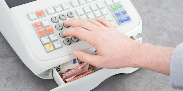 Nearly empty cash register on table from top view with man hands