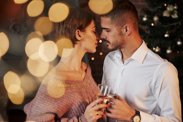Nearly the kiss. nice couple celebrating new year indoors with classic beautiful clothes on they