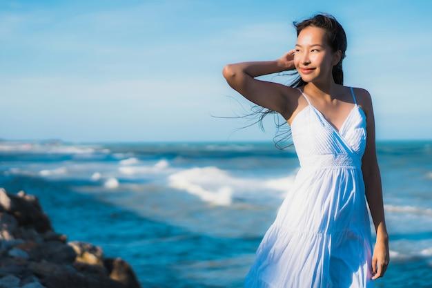 Улыбка красивой молодой азиатской женщины портрета счастливая ослабляет около пляжа и моря neary