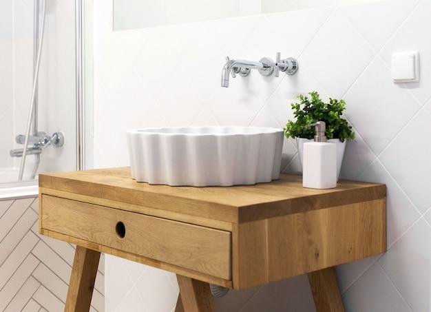 Аккуратная и современная раковина, украшенная вазой, запечатлена в белой ванной комнате.