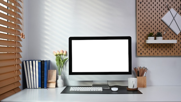 흰색 테이블에 컴퓨터, 책, 사무용품이 있는 깔끔하고 정돈된 작업 공간.