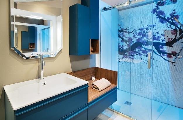 青いシャワー室と壁に取り付けられたキャビネットと反射のある鏡の下に新鮮な巻いたタオルが付いた洗面化粧台を備えたすっきりとしたバスルームのインテリア