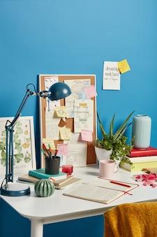 노트북, 책상 램프, 커피, 실내 식물 및 교육용 흰색 책상에 스티커 메모가있는 깔끔한 아늑한 직장.