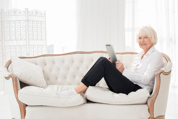 Neat old woman sitting on sofa with a tablet