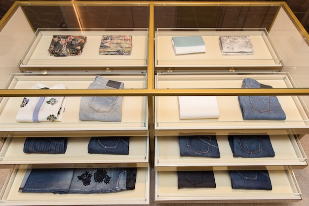 Neat stacks of folded jeans and t-shirt on the shop shelves.