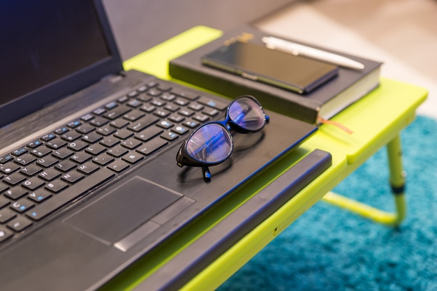 Neat tabletop workstation with eyeglasses lying on the keyboard of an open laptop computer with a diary and mobile phone alongside