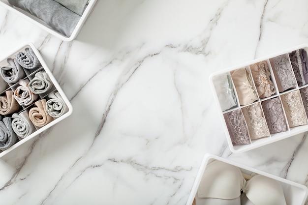 Аккуратно сложенное нижнее белье в разделителе ящика органайзера на белом мраморном фоне